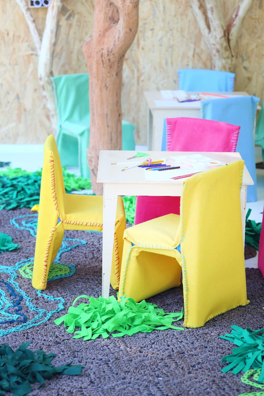 Simple PLASTIC chairs, that are low-cost and readily available, are slip covered in FELT with oversize stitching to emphasis softness and cocoon and resulting in fun comfortable seating, with covers that can be removed and washed. The tables by Pedersen & Lennard are made of birch PLYWOOD.